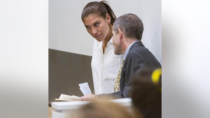 U.S. women's soccer team goalkeeper Hope Solo listens to her attorney Todd Maybrown in Kirkland Municipal Court on Monday, June 23, 2014, in Kirkland, Wash. Solo has entered a not guilty plea following her domestic violence arrest at her sister's home in suburban Seattle. (AP Photo/Pool, The Seattle Times, Mike Siegel, Pool)