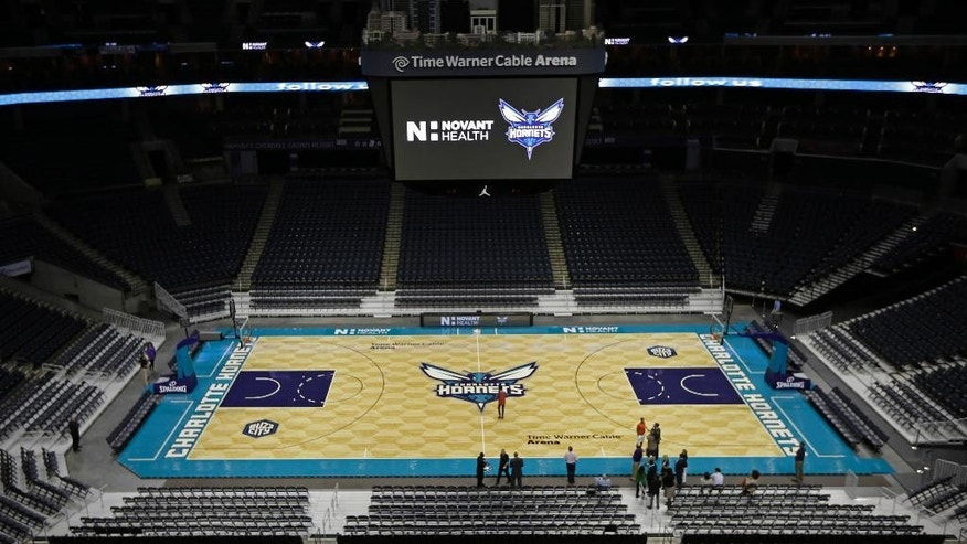 Members of the media photograph the arena floor of the Charlotte Hornets during a news conference to unveil the design for their home court in Charlotte, N.C., Thursday, June 26, 2014. (AP Photo/Chuck Burton)