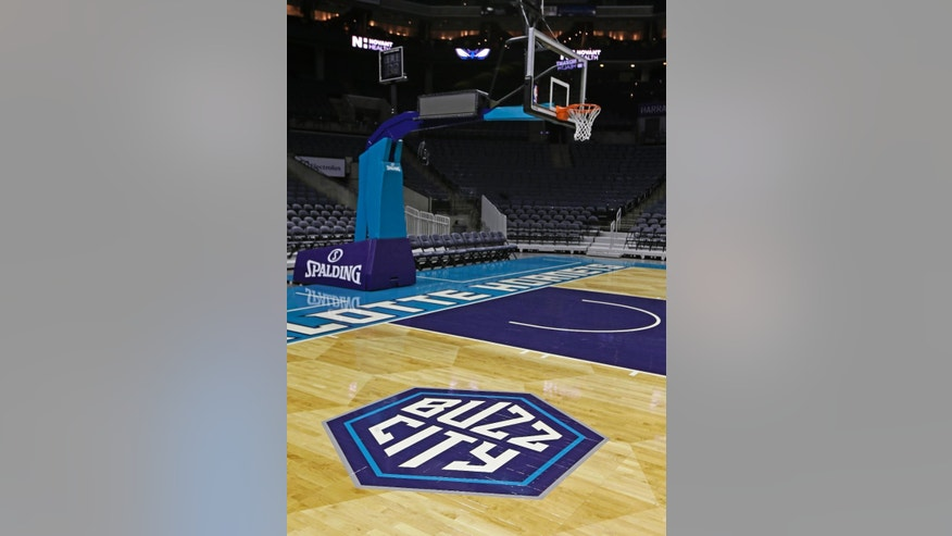A 'Buzz City' logo is shown on the arena floor for the Charlotte Hornets during a news conference to unveil the design for their home court in Charlotte, N.C., Thursday, June 26, 2014. (AP Photo/Chuck Burton)