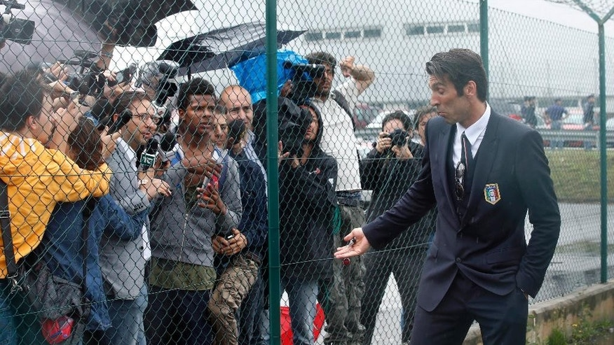Italy goalkeeper Gianluigi Buffon talks to reporters upon his arrival with his teammates at Malpensa airport after landing from Brazil, in Milan, Italy, Thursday, June 26, 2014. Italy was disqualified from the World Cup after loosing to Uruguay in their group stage round.  (AP Photo/Luca Bruno)