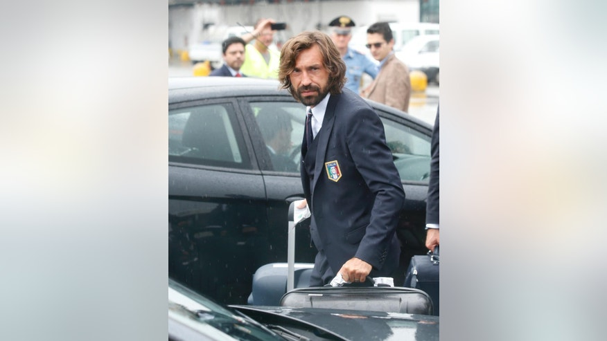 Italy soccer player Andrea Pirlo carries his luggage upon his arrival with his teammates at Malpensa airport after landing from Brazil, in Milan, Italy, Thursday, June 26, 2014.Pirlo recently quit the national team. Pirlo had said before the tournament he would quit international football after Brazil. Italy was disqualified from the World Cup after loosing to Uruguay in their group stage round.  (AP Photo/Luca Bruno)