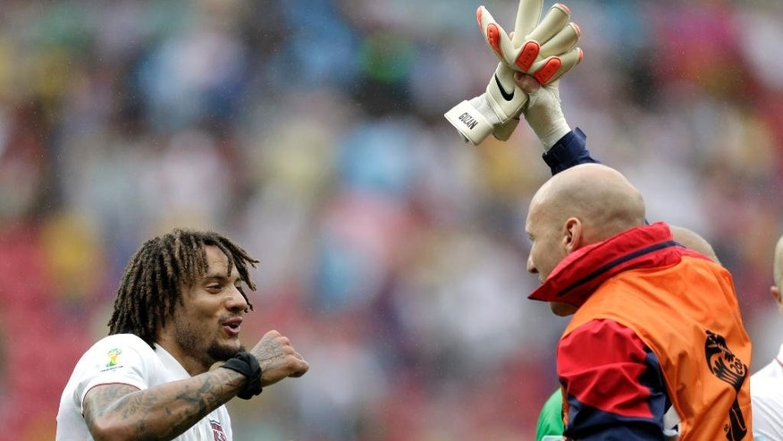 United States' Jermaine Jones, left, celebrates with a teammate after qualifying for the next World Cup round following their 1-0 loss to Germany during the group G World Cup soccer match between the USA and Germany at the Arena Pernambuco in Recife, Brazil, Thursday, June 26, 2014. (AP Photo/Julio Cortez)