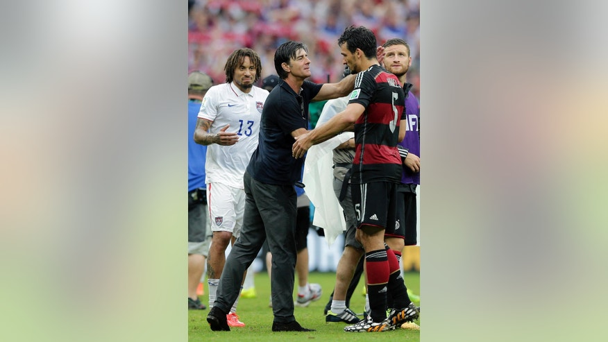 United States' Jermaine Jones, left, looks on as Germany's head coach Joachim Loew hugs Mats Hummels, right, after the group G World Cup soccer match between the USA and Germany at the Arena Pernambuco in Recife, Brazil, Thursday, June 26, 2014. (AP Photo/Matthias Schrader)