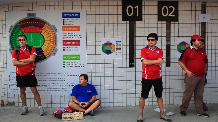 In this  June 18, 2014, photo, Chilean supporters wait for ticket sellers before the starting of the group B World Cup soccer match between Spain and Chile at the Maracana Stadium in Rio de Janeiro, Brazil, Wednesday. Selling tickets to sporting events for prices higher than face value is a crime in Brazil punishable by up to, two years in prison. Accused scalpers are taken to police stations and released after signing a document pledging to show up for a court date. (AP Photo/Bernat Armangue)