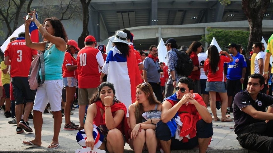 "In this June 18, 2014, photo, Chile soccer fans wait for scalpers, with a sign written in Spanish that reads ""We buy tickets for Chile/Spain"", before the starting of the group B World Cup soccer match between Spain and Chile outside the Maracana Stadium in Rio de Janeiro, Brazil.  As fans from around the world hold up hand-scrawled signs identifying themselves as ticket buyers, undercover police work the crowds as potential buyers and take into custody alleged scalpers from countries ranging from Britain to Russia accused of trying to unload tickets for prices higher than the official FIFA price range of $90 to $175. (AP Photo/Bernat Armangue)"