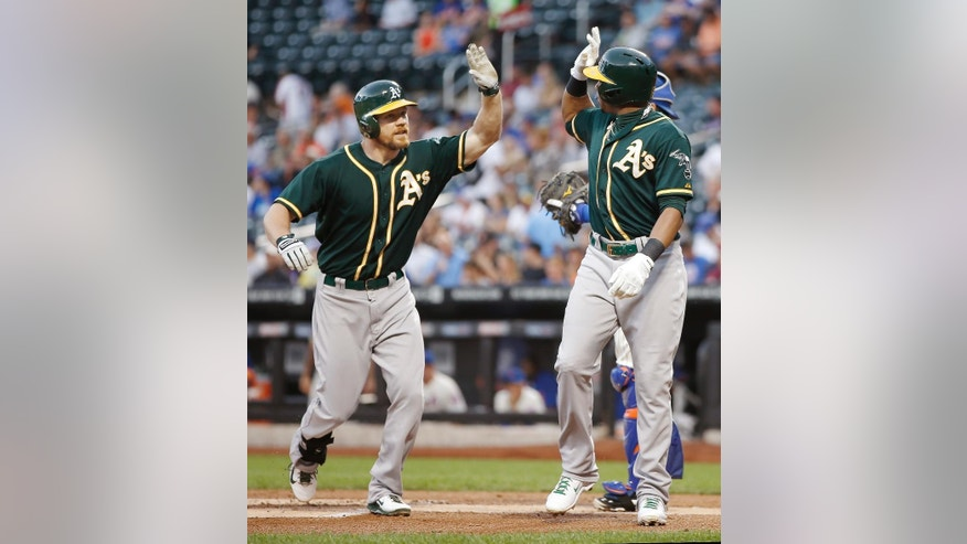 Oakland Athletics Brandon Moss, left, greets Athletics Yoenis Cespedes at the plate after hitting a first-inning, two-run home run off New York Mets starting pitcher Zack Wheeler in an interleague baseball game in New York, Wednesday, June 25, 2014. (AP Photo/Kathy Willens)