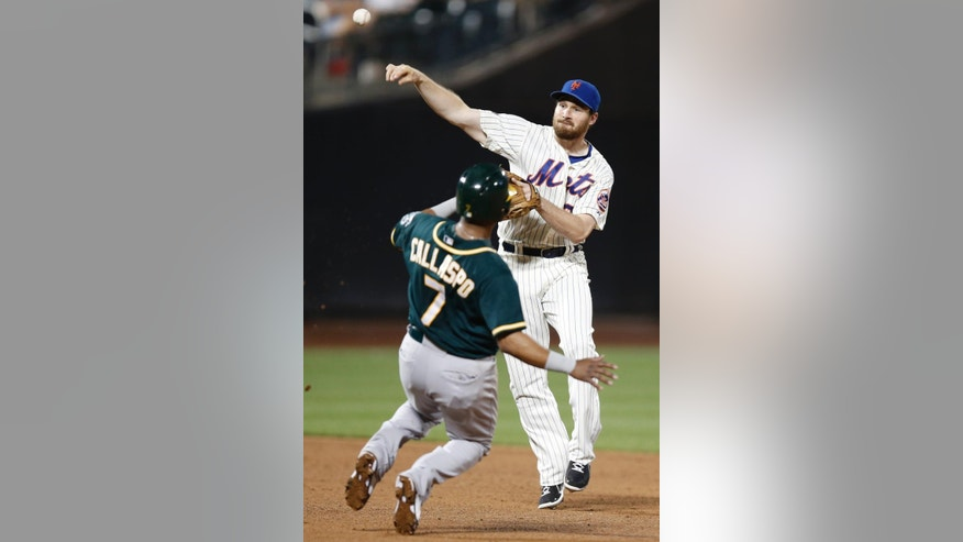 New York Mets second baseman Daniel Murphy (28) throws to first after forcing out Oakland Athletics Alberto Callaspo (7) on a double play after the Athletics Brad Mills (49) grounded into the sixth-inning double play in an interleague baseball game in New York, Wednesday, June 25, 2014. The Athletics Josh Reddick scored on the play. (AP Photo/Kathy Willens)