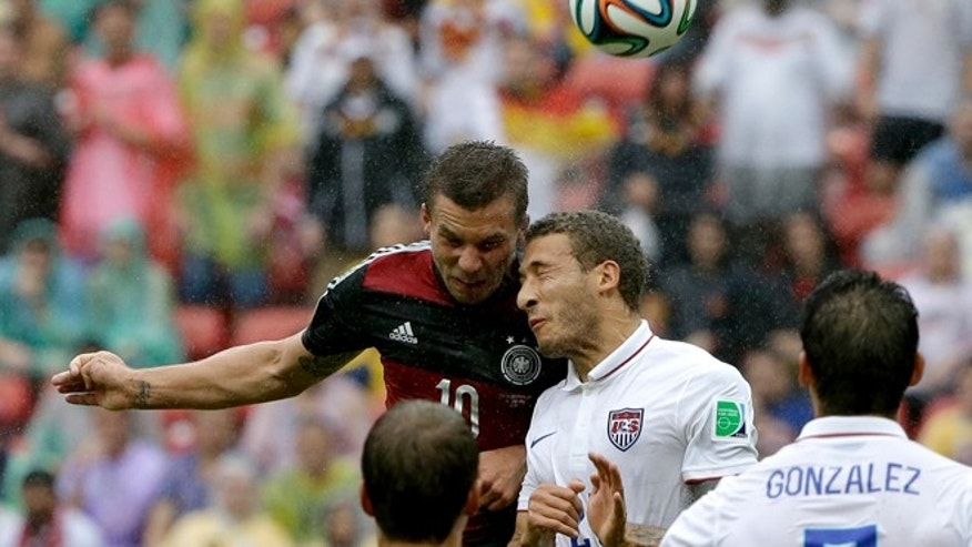 Germany's Lukas Podolski heads the ball against United States' Fabian Johnson.
