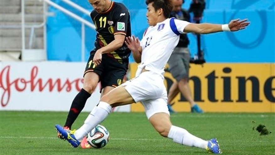 Belgium's Kevin Mirallas and South Korea's Lee Yong at the Itaquerao Stadium in Sao Paulo, Thursday, June 26, 2014.