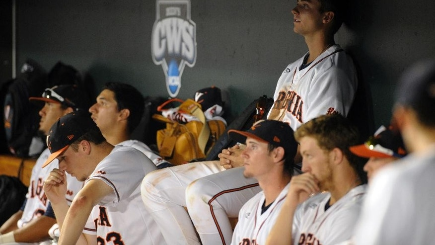 Virginia players sit in the dugout after a 3-2 loss to Vanderbilt in the deciding game of the best-of-three NCAA baseball College World Series finals in Omaha, Neb., Wednesday, June 25, 2014. (AP Photo/Eric Francis)