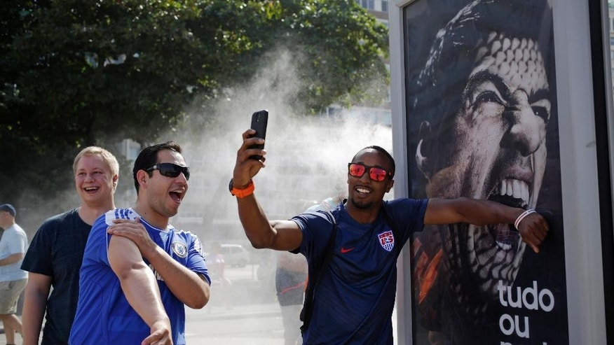 A U.S. soccer fan pretends that Uruguay's soccer striker Luis Suarez is biting him as he takes a selfie next to an Adidas advertisement featuring Suarez near Copacabana beach in Rio de Janeiro, Brazil, Thursday, June 26, 2014. FIFA banned Suarez from all football activities for four months on Thursday for biting an opponent at the World Cup, a punishment that rules him out of the rest of the tournament. (AP Photo/Matt Dunham)