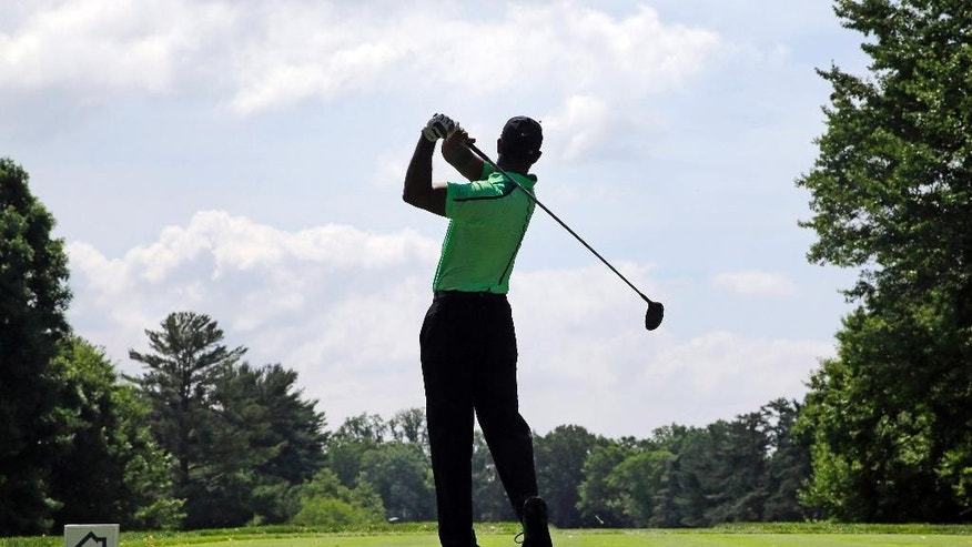 Tiger Woods watches his tee shot on the third hole during the first round of the Quicken Loans National PGA golf tournament, Thursday, June 26, 2014, in Bethesda, Md. (AP Photo/Patrick Semansky)