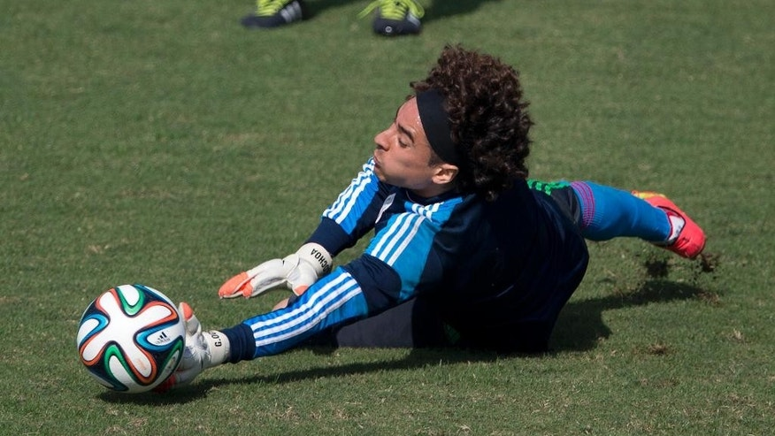 Mexico goalkeeper Guillermo Ochoa reaches to grab a ball during a training session in Santos, Brazil, Thursday, June 26, 2014. Mexico will face the Netherlands in their next World Cup match in Fortaleza, Sunday. (AP Photo/Eduardo Verdugo)