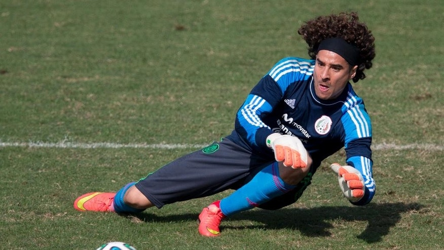 Mexico goalkeeper Guillermo Ochoa leaps to trap a ball during a training session in Santos, Brazil, Thursday, June 26, 2014. Mexico will face the Netherlands in their next World Cup match in Fortaleza, Sunday. (AP Photo/Eduardo Verdugo)