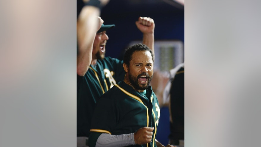 Oakland Athletics player Coco Crisp reacts after a video review showed he scored the go-ahead run during the ninth inning of a baseball game in Miami against the Miami Marlins, Friday, June 27, 2014. The A's won 9-5. (AP Photo/J Pat Carter)