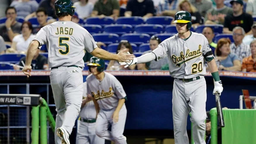 Oakland Athletics' John Jaso (5) is congratulated by Josh Donaldson (20) after Jaso and Coco Crisp (not shown) scored on a single by Brandon Moss during the first inning of a baseball game against the Miami Marlins, Saturday, June 28, 2014, in Miami. (AP Photo/Wilfredo Lee)