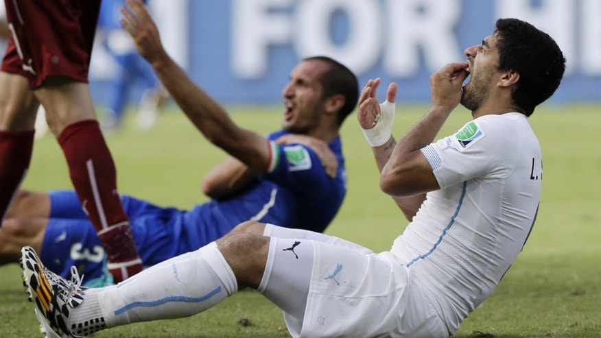 June 24, 2014: In this file photo, Uruguay's Luis Suarez holds his teeth after biting Italy's Giorgio Chiellini's shoulder during the group D World Cup soccer match between Italy and Uruguay at the Arena das Dunas in Natal, Brazil.