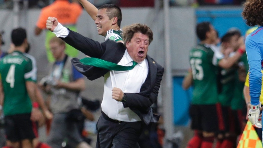 In this June 23, 2014 photo, Mexico's head coach Miguel Herrera celebrates after Mexico's Andres Guardado  scored his side's second goal during the group A World Cup soccer match between Croatia and Mexico at the Arena Pernambuco in Recife, Brazil. Mexicoâs national soccer coach just canât keep his joy bottled up, and his enthusiasm has made him one of the most entertaining and popular figures of the World Cup and an Internet sensation worldwide. (AP Photo/Petr David Josek)