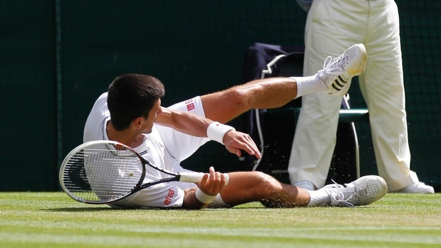 Novak Djokovic of Serbia falls onto his shoulder during the men's singles match against Gilles Simon of France at the All England Lawn Tennis Championships in Wimbledon, London, Friday, June 27, 2014. (AP Photo/Sang Tan)