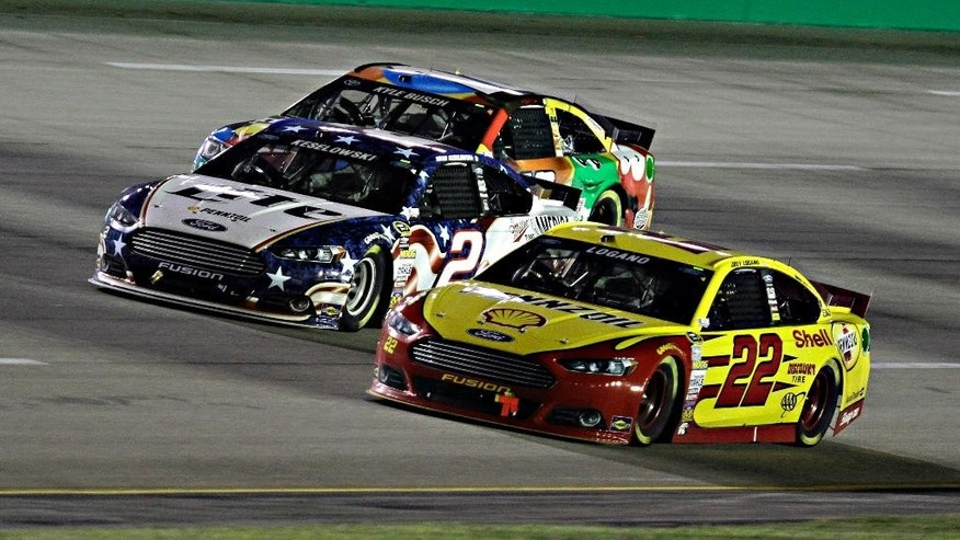 Joey Logano (22) gets a nose in front of Brad Keselowski (2) on the final restart of the NASCAR Sprint Cup series auto race Saturday, June 28, 2014, at Kentucky Speedway in Sparta, Ky. In the background is Kyle Busch. Keselowski won the race. (AP Photo/Garry Jones)