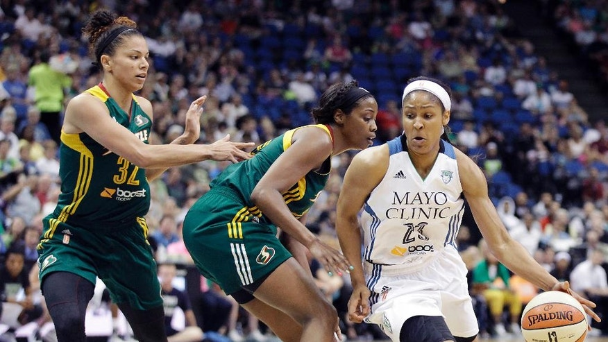 Minnesota Lynx forward Maya Moore (23) pushes the ball around Seattle Storm forward Camille Little, center, and forward Alysha Clark (32) in the first half of a WNBA basketball game, Sunday, June 29, 2014, in Minneapolis. (AP Photo/Stacy Bengs)
