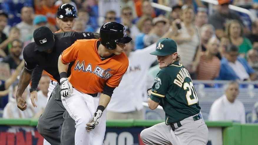 Miami Marlins' Christian Yelich,left, heads for home as Oakland Athletics third baseman Josh Donaldson, right, is unable to hang on to a throw by second baseman Alberto Callaspo during the first inning of a baseball game, Sunday, June 29, 2014 in Miami. Yelich tripled to deep center and scored on throwing error by Callaspo. (AP Photo/Wilfredo Lee)