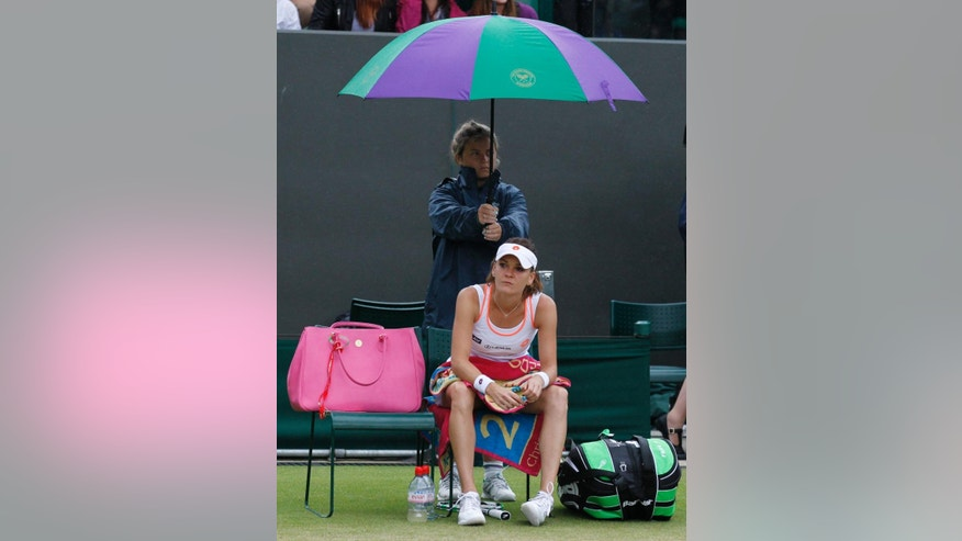 Agnieszka Radwanska of Poland sits in her chair underneath an umbrella as rain falls and the women's singles match against Ekaterina Makarova of Russia is suspended at the All England Lawn Tennis Championships in Wimbledon, London, Monday, June 30, 2014. (AP Photo/Sang Tan)