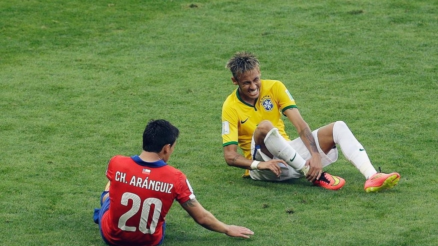 Brazil's Neymar grimaces after being tackled by Chile's Charles Aranguiz during the World Cup round of 16 soccer match between Brazil and Chile at the Mineirao Stadium in Belo Horizonte, Brazil, Saturday, June 28, 2014. (AP Photo/Hassan Ammar)