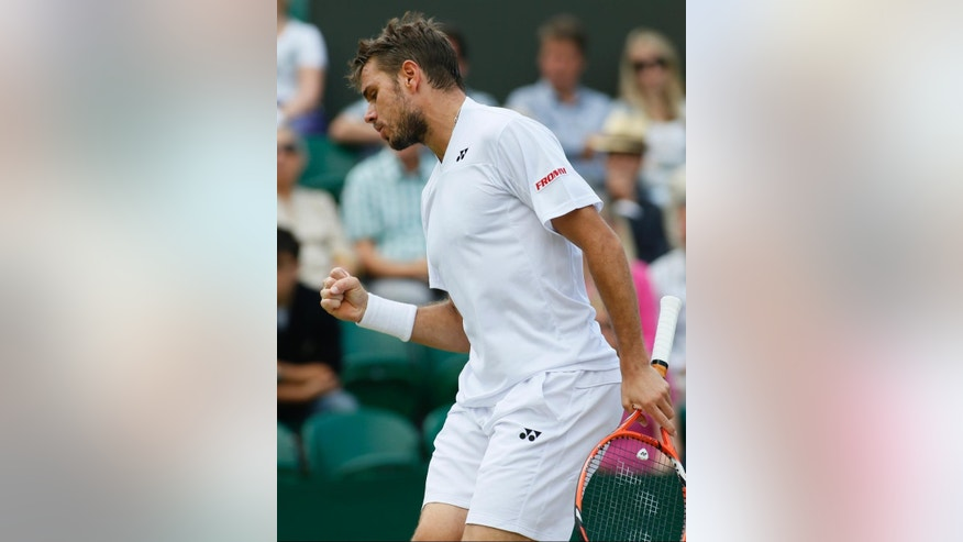 Stan Wawrinka of Switzerland celebrates a point to Denis Istomin of Uzbekistan during their match at the All England Lawn Tennis Championships in Wimbledon, London, Monday, June 30, 2014. (AP Photo/Alastair Grant)