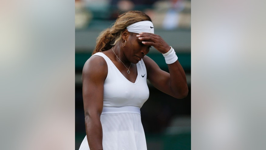 Serena Williams of U.S. gestures after losing a point to Alize Cornet of France during their women's singles match at the All England Lawn Tennis Championships in Wimbledon, London, Saturday, June 28, 2014. (AP Photo/Sang Tan)