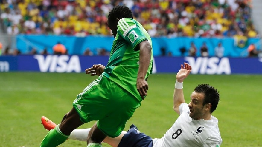 France's Mathieu Valbuena, right, slides in to kick the ball away from Nigeria's Ahmed Musa during the World Cup round of 16 soccer match between France and Nigeria at the Estadio Nacional in Brasilia, Brazil, Monday, June 30, 2014. (AP Photo/Petr David Josek)