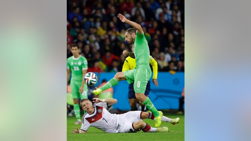 Algeria's Medhi Lacen clears the ball from Germany's Bastian Schweinsteiger during the World Cup round of 16 soccer match between Germany and Algeria at the Estadio Beira-Rio in Porto Alegre, Brazil, Monday, June 30, 2014. (AP Photo/Sergei Grits)