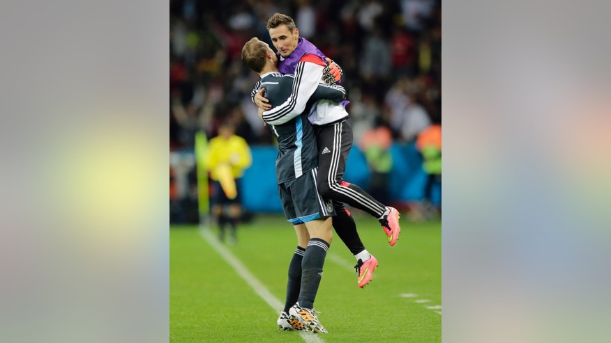 Germany's Miroslav Klose, right, jumps in goalkeeper Manuel Neuer's arms after Germany scored their first goal in overtime during the World Cup round of 16 soccer match between Germany and Algeria at the Estadio Beira-Rio in Porto Alegre, Brazil, Monday, June 30, 2014. (AP Photo/Matthias Schrader)
