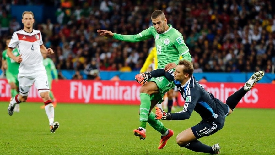 Germany's goalkeeper Manuel Neuer, right, clears the ball from Algeria's Islam Slimani during the World Cup round of 16 soccer match between Germany and Algeria at the Estadio Beira-Rio in Porto Alegre, Brazil, Monday, June 30, 2014. (AP Photo/Frank Augstein)