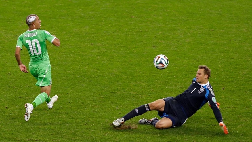 Germany's goalkeeper Manuel Neuer, right, clears a ball ahead of Algeria's Sofiane Feghouli during the World Cup round of 16 soccer match between Germany and Algeria at the Estadio Beira-Rio in Porto Alegre, Brazil, Monday, June 30, 2014. (AP Photo/Thanassis Stavrakis)
