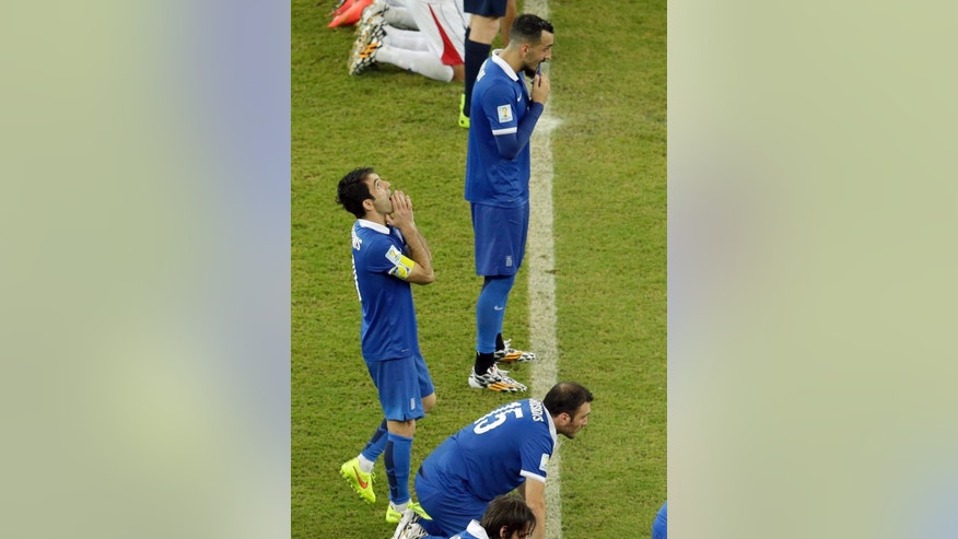 Greece's Giorgos Karagounis, left, and his teammates wait in the center circle during the penalty shoot-out of the World Cup round of 16 soccer match between Costa Rica and Greece at the Arena Pernambuco in Recife, Brazil, Sunday, June 29, 2014. Costa Rica won 5-3 on penalties and advanced to the quarterfinal.  (AP Photo/Hassan Ammar)