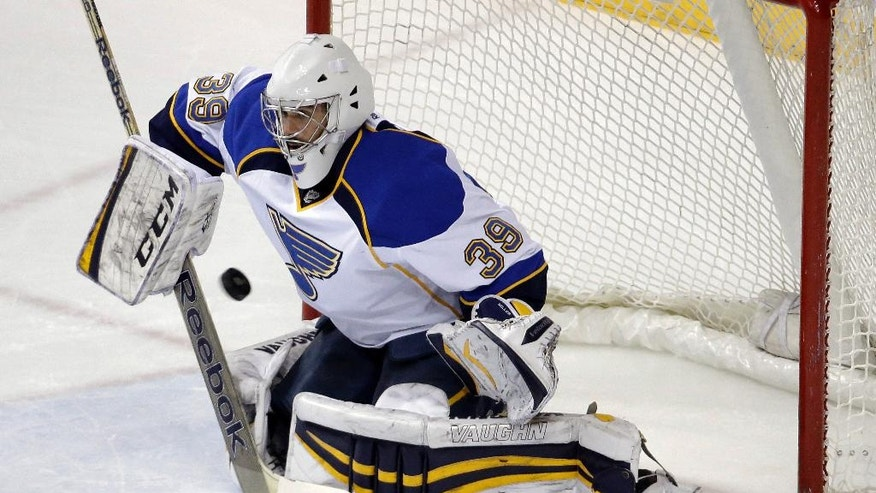 FILE - In this March 6, 2014 file photo, St. Louis Blues goalie Ryan Miller blocks a shot against the Nashville Predators in the first period of an NHL hockey game in Nashville, Tenn. NHL teams can begin making deals with free agents Tuesday, July 1, 2014. (AP Photo/Mark Humphrey, File)