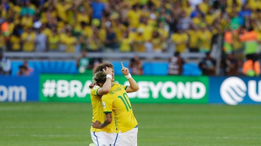 Brazil's Neymar hugs teammate David Luiz after a penalty shootout following regulation time during the World Cup round of 16 soccer match between Brazil and Chile at the Mineirao Stadium in Belo Horizonte, Brazil, Saturday, June 28, 2014. Brazil won 3-2 on penalties after a 1-1 tie. (AP Photo/Ricardo Mazalan)