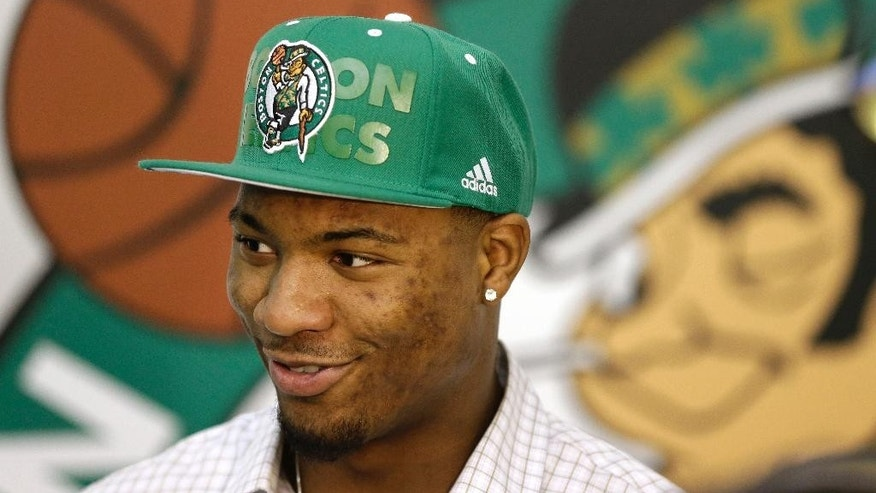 Boston Celtics 2014 NBA basketball draft pick Marcus Smart stands in front of a Boston Celtics logo while speaking with members of the media, Monday, June 30, 2014, in Waltham, Mass. (AP Photo/Steven Senne)