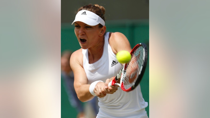 Simona Halep of Romania plays a return to Zarina Diyas of Kazakhstan during their women's singles match at the All England Lawn Tennis Championships in Wimbledon, London, Tuesday, July 1, 2014. (AP Photo/Alastair Grant)