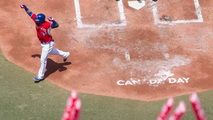 Toronto Blue Jays' Jose Bautista celebrates after hitting a solo homer off Milwaukee Brewers pitcher Marco Estrada during first inning interleague baseball action in Toronto on Tuesday July 1 , 2014. (AP Photo/The Canadian Press, Chris Young)