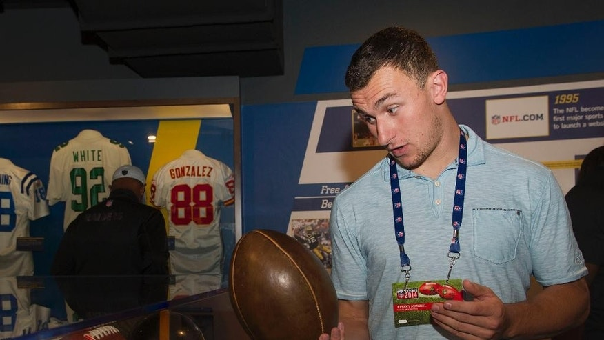 Cleveland Browns rookie Johnny Manziel looks at the size of a replica of a 1906 football,  during the 2014 NFL Rookie Symposium at the Pro Football Hall of Fame in Canton, Ohio, Saturday, June 28, 2014. (AP Photo/Phil Long)