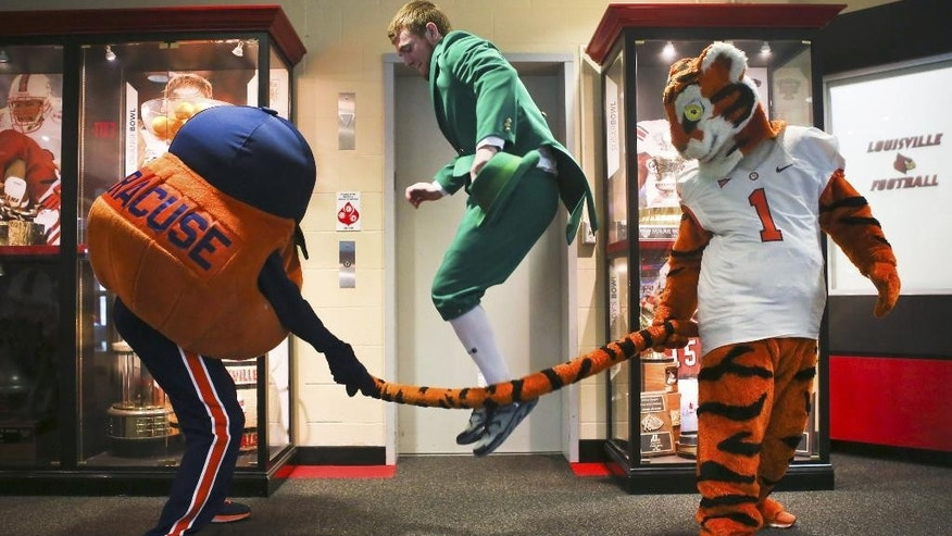 Syracuse mascot Otto the Orange, left, uses the Clemson Tiger's tail as a jump rope for Notre Dame's Leprechaun before the start of the ACC news conference in Louisville, Ky., Tuesday, July 1, 2014. After bouncing around in three other leagues over 19 years, Tuesday marked Louisville's official entry into the ACC. (AP Photo/The Courier-Journal, Alton Strupp)