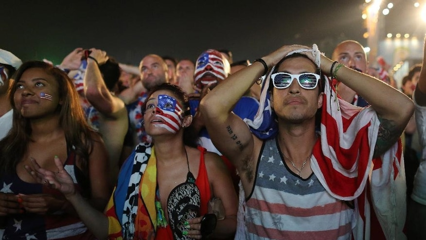 Fans of the United States national soccer team react, in frustration, as they watch their team's World Cup round of 16 match against Belgium on a live telecast inside the FIFA Fan Fest area on Copacabana beach in Rio de Janeiro, Brazil, Tuesday, July 1, 2014. Belgium beat the United States 2-1 in extra time to reach World Cup quarterfinals. (AP Photo/Leo Correa)