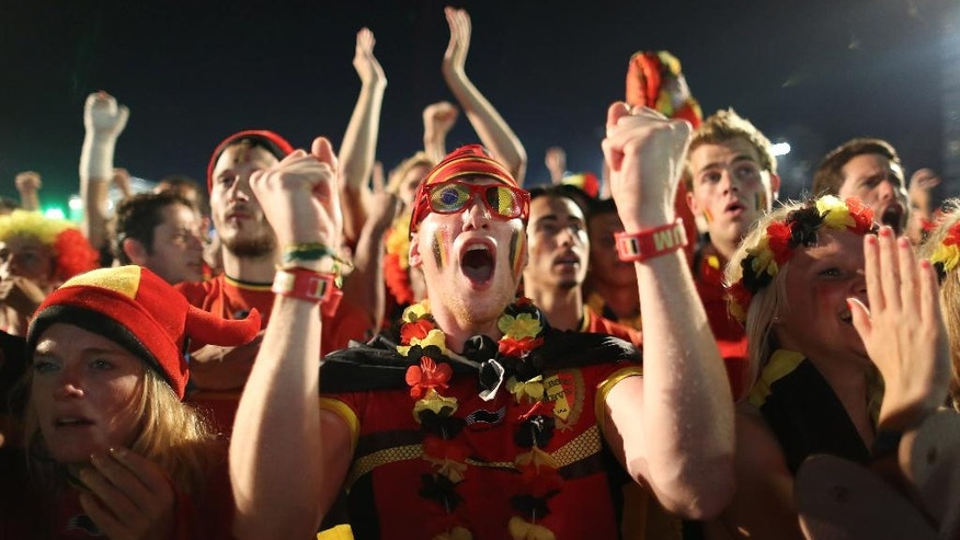 Belgium soccer fans react as they watch their team's World Cup round of 16 match against United States on a live telecast inside the FIFA Fan Fest area on Copacabana beach in Rio de Janeiro, Brazil, Tuesday, July 1, 2014. Belgium beat the United States 2-1 in extra time to reach World Cup quarterfinals. (AP Photo/Leo Correa)
