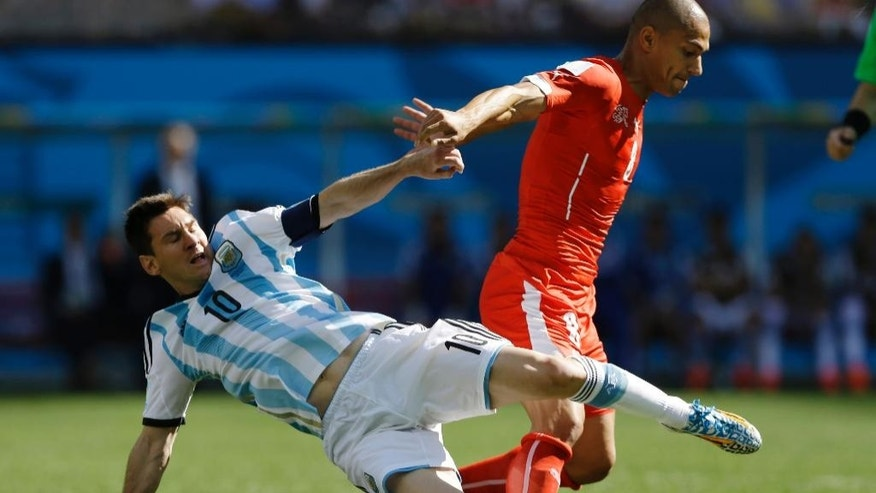 Argentina's Lionel Messi tackles Switzerland's Goekhan Inler during their World Cup round of 16 soccer match at the Itaquerao Stadium in Sao Paulo, Brazil, Tuesday, July 1, 2014. (AP Photo/Kirsty Wigglesworth)