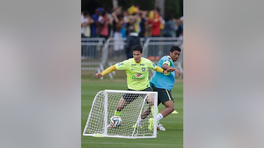 Brazil's Hernanes, left, and Paulinho, practice during a training session at the Granja Comary training center in Teresopolis, Brazil, Monday, June 30, 2014. Brazil will face Colombia on July 4 in a quarter-final match of the 2014 soccer World Cup. (AP Photo/Andre Penner)