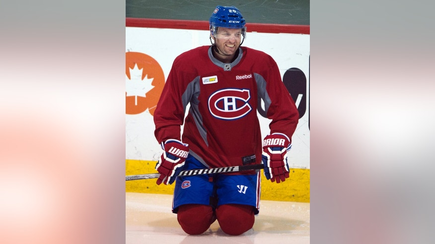 FILE - In this April 14, 2014 file photo, Montreal Canadiens left wing Thomas Vanek stretches during the team's hockey practice in Brossard, Quebec. NHL teams can begin making deals with free agents Tuesday, July 1, 2014.  (AP Photo/The Canadian Press, Ryan Remiorz, File)