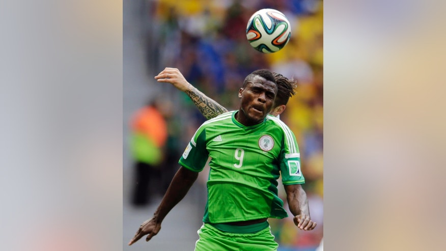 Nigeria's Emmanuel Emenike (9) heads the ball against France's Olivier Giroud during the World Cup round of 16 soccer match between France and Nigeria at the Estadio Nacional in Brasilia, Brazil, Monday, June 30, 2014. (AP Photo/Petr David Josek)