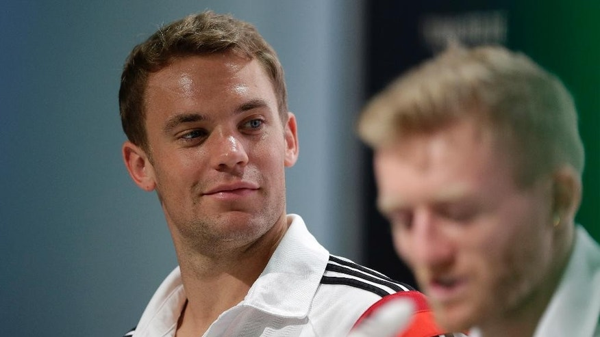 German national soccer team goalkeeper Manuel Neuer, background left, attends a news conference besides teammate Andre Schuerrle in Santo Andre near Porto Seguro, Brazil, Wednesday, July 2, 2014. Germany faces France on upcoming Friday in Maracana Stadium in Rio de Janeiro, in the quarterfinals of the World Cup. (AP Photo/Matthias Schrader)